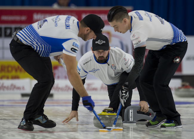 Skip Reid Carruthers watches as sweepers Derek Samagalski (L) and Colin Hodgson guide a rock during the men's final at the 2016 Canada Cup. (Michael Burns/Curling Canada)